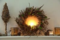 Christmas wreath and candles on mantelpiece