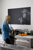 Woman using juicer in contemporary kitchen