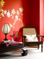 Dark wood oriental style furniture against red wall