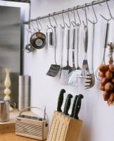 Utensils hanging on butchers hooks in kitchen