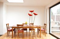 Modern dining room with poppy mural on wall