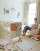 Pregnant woman sitting in baby's nursery
