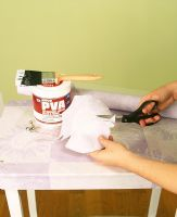 Person cutting wallpaper to cover table