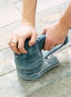 Detail of person using electric sander