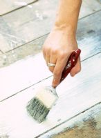 Detail of person painting floorboards