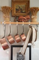 Shelf in country kitchen with copper pans