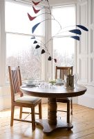 Modern mobile above small round dining table