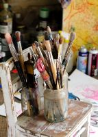 Collection of paint brushes on chair in artist's studio