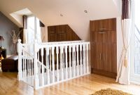 White bannisters and built in cupboards in modern loft room