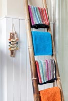 Colourful towels on bamboo rail