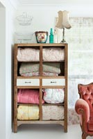 Floral eiderdowns displayed in vintage cabinet