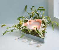 Christmas decoration of Mistletoe and heart shaped candle