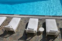 White sunbeds by pool
