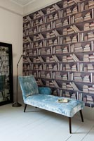 Chaise lounge and patterned wallpaper