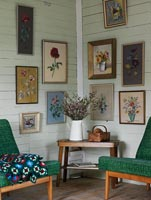 Display of floral paintings on living room wall
