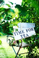 Time for tea sign on garden chair