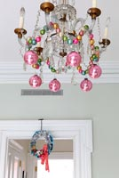 Christmas baubles hanging from chandelier