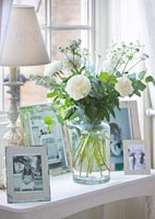 Low table with display of photos and Roses in vase
