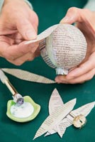 Create a simple Christmas bauble using newspaper -  attaching strips of paper to bauble