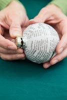 Create a simple Christmas bauble using newspaper -  placing cap back on to bauble
