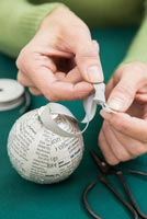 Create a simple Christmas bauble using newspaper - attaching ribbon and tieing a knot