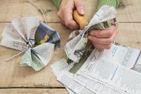 Creating a simple Christmas wreath using newspaper and  wire - making a hole through the newspaper