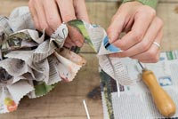 Creating a simple Christmas wreath using newspaper and  wire - adding section to wreath