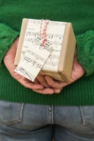 Woman hiding christmas present wrapped with music sheet paper