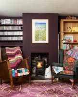 Colourful armchairs by fireplace