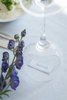 Name tag under wine glass with Aconitum flower