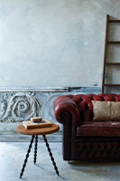 Wooden side table and leather chesterfield sofa