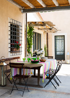 Colourful dining area under pergola