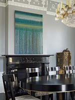Modern painting hung above classic fireplace