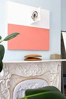 Abstract painting above ornate fireplace
