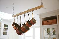 Copper pots hanging from rail