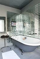 Roll top bath surrounded by mirrored tiles