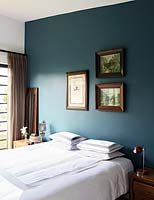 Framed paintings above bed