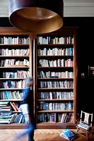 Woman walking past bookcase