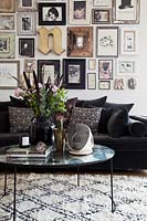 Display of framed photos and art above sofa