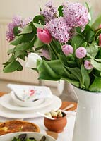 Jug of Tulips and Hyacinth flowers on dining table