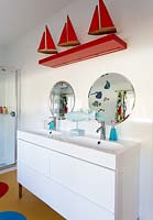 Bathroom sinks with colourful toys and ornaments