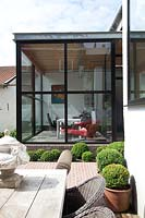 Modern extension and patio with topiary