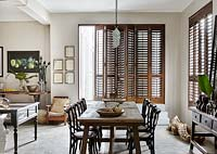 Open plan dining area with wooden shutters