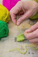Making christmas pompom decorations - Once youve threaded the separate length of wool through the fork, tie a knot and pull tightly