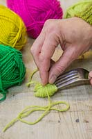 Making christmas pompom decorations - Gently remove the bundle of wool from the fork