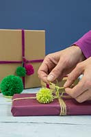 Making christmas pompom decorations - Attaching a wool pompom to a christmas present