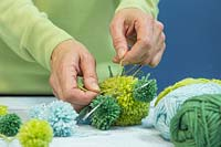 Making a pompom star decoration - Tying wool pompoms to a metal frame in the shape of a star
