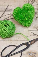 A green heart pompom made from wool