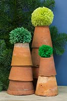 Wool pompoms on top of terracotta pots