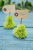 Miniature Christmas trees made from wool pompoms with place setting name cards